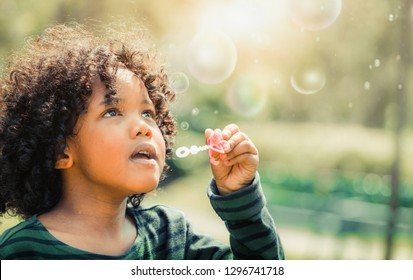 Happy little kid blowing soap bubble in school garden. Child outdoor activity concept.