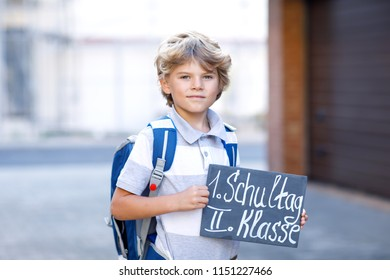 """Happy little kid boy with backpack or satchel. Schoolkid on the way to school. Healthy adorable child outdoors On desk """"First day second grade"""" in German. Back to school."""