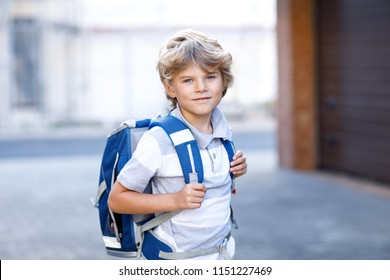 Happy little kid boy with backpack or satchel. Schoolkid on the way to school. Healthy adorable child outdoors on the street leaving home. Back to school.