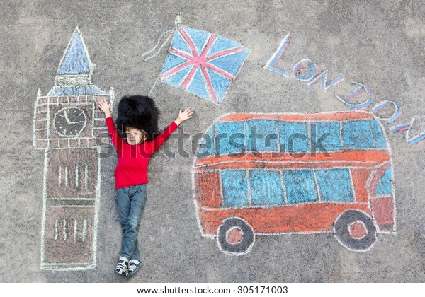 Happy little kid boy in british queen's guard soldier uniform having fun with London picture drawing with colorful chalks. With Big Ben, Union Jack and red bus. Creative leisure with children outdoors