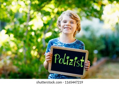 Happy little kid boy with chalk desk in hands. Healthy adorable child outdoors On desk - police officer - in German as dream profession of beautiful schoolkid