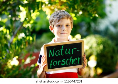 Happy little kid boy with chalk desk in hands. Healthy adorable child outdoors On desk - natural scientist - in German as dream profession of beautiful schoolkid