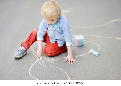 Happy little kid boy drawing with colored chalk on asphalt. Creative leisure for toddler child in summer park. Street art, kids education.