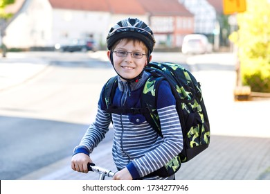 Happy little kid boy with glasses and backpack or satchel on scooter. Schoolkid on way to school. Healthy adorable child outdoors. Back to school after quarantine time from corona pandemic disease