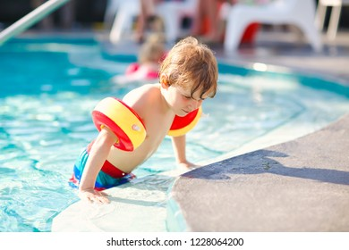Happy little kid boy having fun in an swimming pool. Active happy healthy preschool child learning to swim. with safe floaties or swimmies. Family, vacations, summer concept