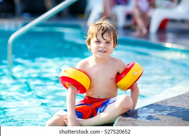 Happy little kid boy having fun in an swimming pool. Active happy child learning to swim. with floaties or swimmies. Family, vacations, summer concept.