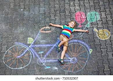 Happy little kid boy having fun with bicycle and air balloons picture drawing with colorful chalks on ground. Children, lifestyle, fun concept. funny child playing and dreaming of future