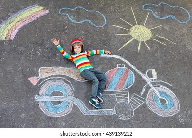 Joyeux petit garçon en casque s'amusant avec une photo de moto dessinant avec des craies colorées. Enfants, mode de vie, concept amusant. enfant rêvant d'avenir et de métier.