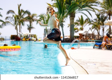Happy little kid boy jumping in the pool and having fun on family vacations in a hotel resort. Healthy child playing in water