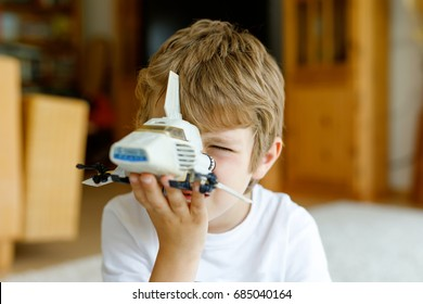 Happy little kid boy playing with space shuttle toy. Cute child in having fun in the morning before school. Closeup of face and old toy