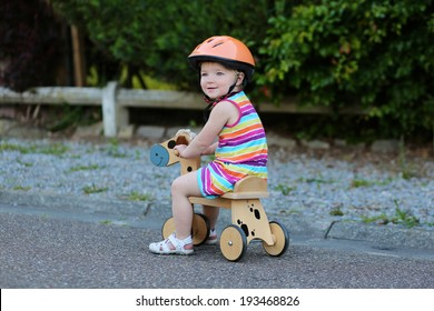 134aa105203 Happy little kid, cute blonde toddler girl in colorful dress and orange  safety helmet playing