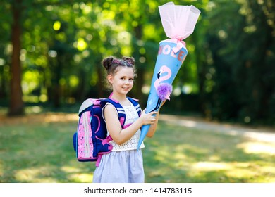 Happy little kid girl with backpack or satchel and big school bag or cone traditional in Germany for the first day of school. Healthy adorable child outdoors, in green park.