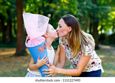 Happy little kid girl and mother with big traditional school gift cone in Germany. schoolkid on first day of elementary class. Back to school concept. Healthy child and woman kissing and hugging,