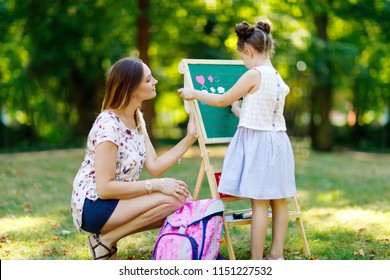 Happy little kid girl and mother by big chalk desk Preschool or schoolkid on first day of elementary class. Back to school concept. Healthy child and woman writing and painting outdoors