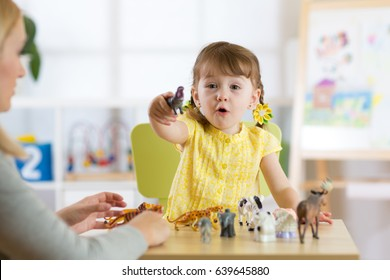 Happy little kid girl. Smiling child toddler playing animal toys at home or kindergarten.
