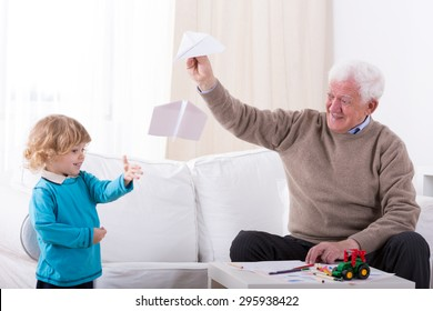 Happy little kid letting with grandfather paper airplane