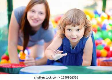 Happy little kid playing at colorful plastic balls with her mother or nanny, playground high view. Adorable girl having fun indoors, kindergarten