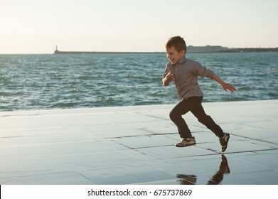 happy little kid running along the sea coast in the city at warm sunset