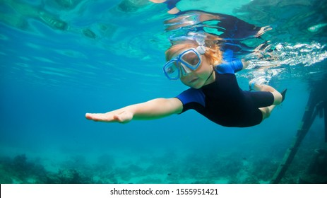 Happy little kid in snorkeling mask and wetsuit jump and dive underwater in coral reef sea lagoon. Family travel lifestyle in summer adventure camp. Swimming activities on beach vacation with child.