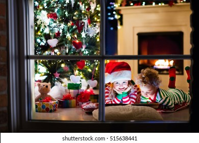Happy little kids in matching red and green striped pajamas decorate Christmas tree in beautiful living room with traditional fire place. Children opening presents on Xmas eve. - Shutterstock ID 515638441