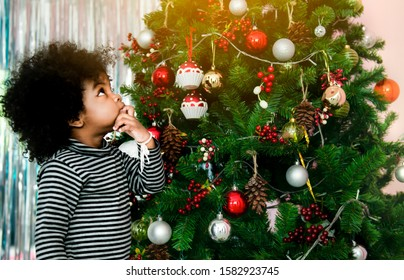 Happy a little mixed-race girl and Afro-American hair playing colorful toy with a Christmas tree background.A dark skin kid have funny with family Xmas morning in decorated living room.Christmas Eve.