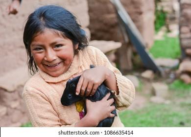 Happy little native american girl holding her black guinea pig.