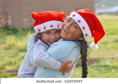 Happy little native american sisters hugging outdoors. Children wear typical Santa Claus red hat.