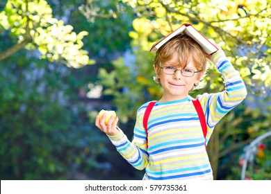 Happy little preschool kid boy with glasses, books, apple and backpack on his first day to school or nursery. Child outdoors on warm sunny day, Back to school concept