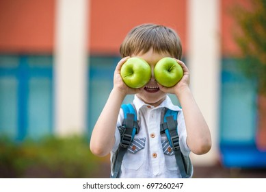 Happy little preschool kid boy with two green apples like his eyes. Boy behind shoulders have backpack. First day to school or nursery. Warm day in an early autumn. Back to school concept.