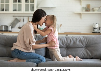 Happy little preschooler girl and young mother touch noses foreheads look in eyes enjoy tender sweet moment together, smiling loving mom and daughter have fun playing together at home on weekend