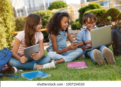 Happy little school children with digital gadgets with and backpacks sitting at the grass park outdoors