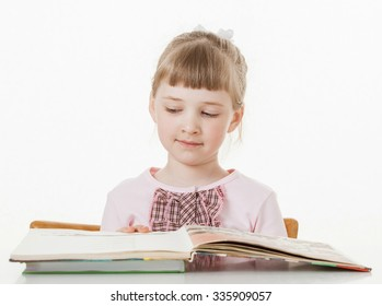 Happy little school girl learning to read, white background
