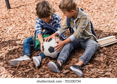 happy little schoolboys playing with soccer ball while sitting on playground