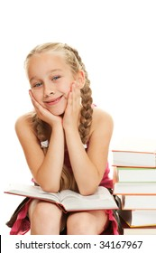 Happy little schoolgirl sitting on a stack of books