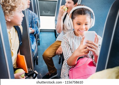 happy little schoolgirl using smartphone and listening music with headphones while riding on school bus with classmates