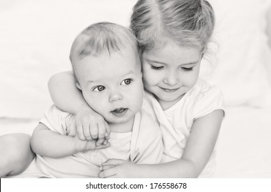 happy little sister hugging her brother on a white background ( black-white )