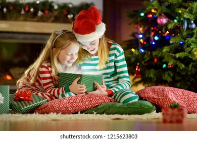 Happy little sisters wearing Christmas pajamas opening gift boxes by a fireplace in a cozy dark living room on Christmas eve. Celebrating Xmas at home.