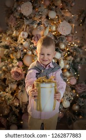 Happy little smiling boy with christmas gift box. New year and Christmas.