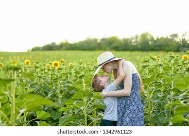 Happy little son kissing pregnant mother standing on the field of blooming sunflowers.