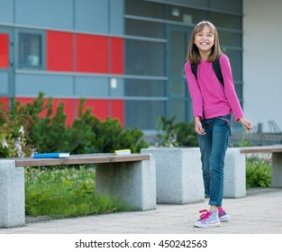 Happy little student with backpack excited to be back to school. Beginning of class after vacation. Full length outdoor portrait.