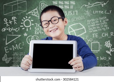 Happy little student showing empty tablet screen in the class while wearing glasses and smiling at the camera