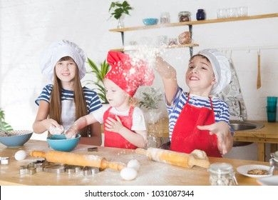 happy little three children chefs preparing cookies in the kitchen.