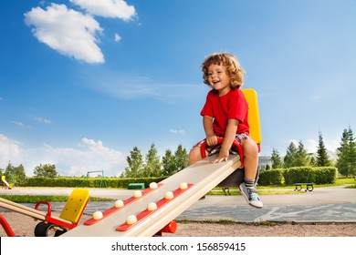 Happy little three years old child riding seesaw with big smile and happy face