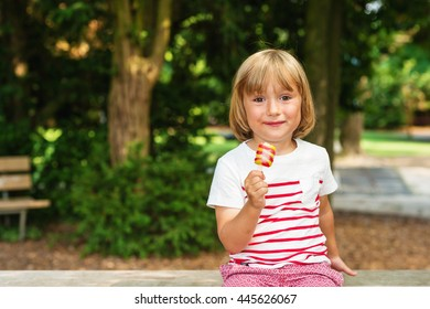 Happy little toddler boy eating colorful ice cream in summer, outdoors.