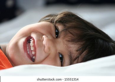 Happy little toddler boy lying down and smiling