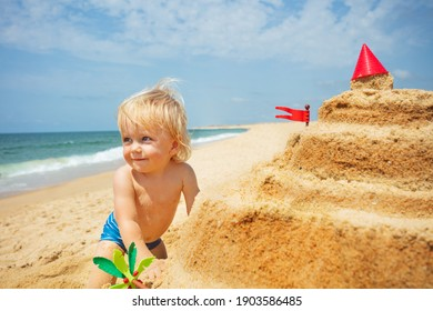 Happy little toddler boy portrait near sand castle on the sea beach