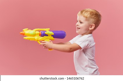 Happy little toddler boy  in summer clothes holds toy water gun isolated on pink wall background. Children studio portrait. People childhood lifestyle concept.