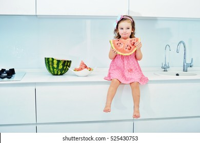 Happy little toddler girl eating fresh ripe watermelon for healthy breakfast in a white sunny family kitchen. Baby on the table at home.