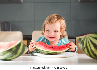 Happy little toddler girl eating fresh ripe watermelon in kitchen. Healthy Eating