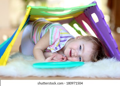Happy little toddler girl playing hide and seek and learning numbers with colorful soft puzzles